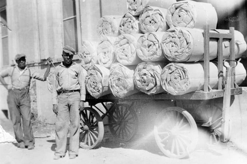 Parchman #17: Workers pose with rolls of (cotton wrapped in?) canvas loaded on a wagon at Parchman Farm circa 1930.