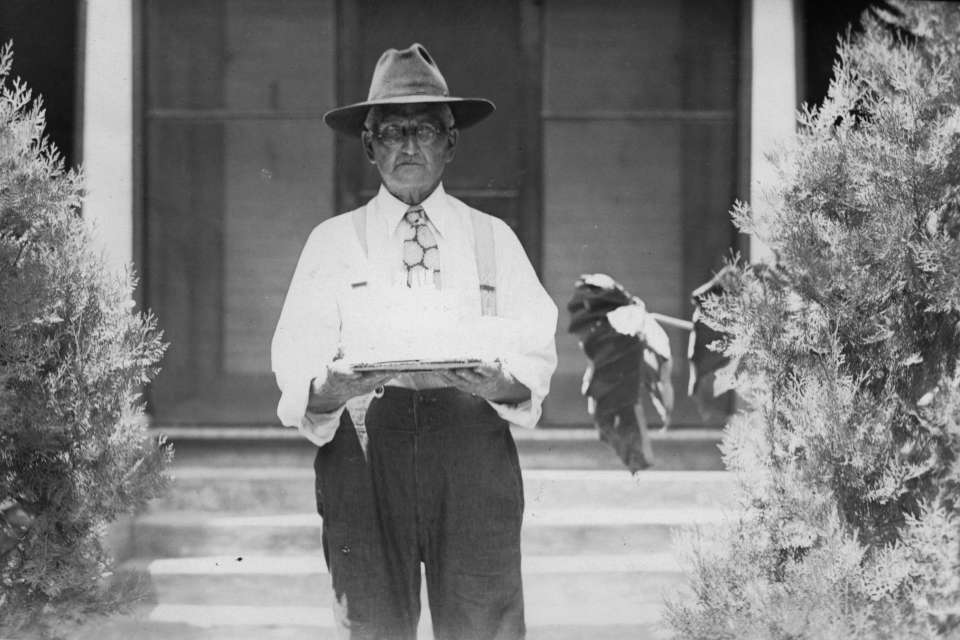 """Tabor #2: Parchman legend A. J. """"Pap"""" Tabor carries a cake circa 1930."""